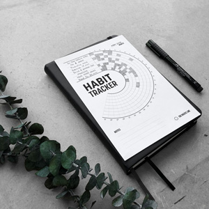 Filled in habit tracker printable laying on a black notebook