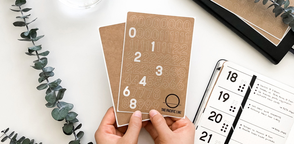 Kraft paper journal number stickers being held in a woman's hands